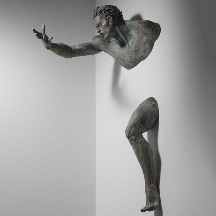 Famous cast bronze figure through wall sculpture
