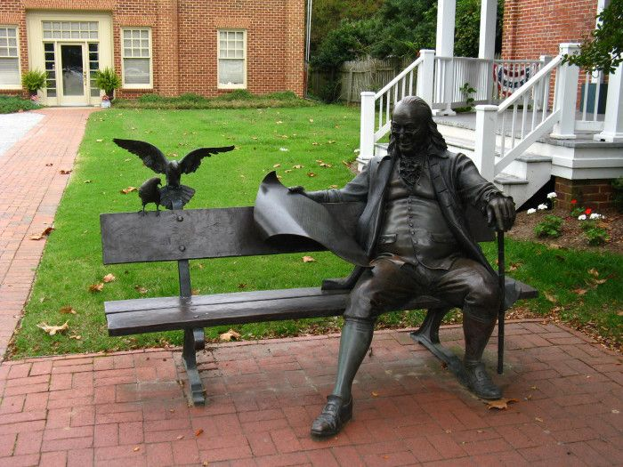 Life Size A sculpture of Benjamin Franklin sitting on the chair reading the Pennsylvania Gazette