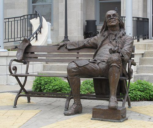 Outdoor bronze franklin sitting on a bench statue for the University