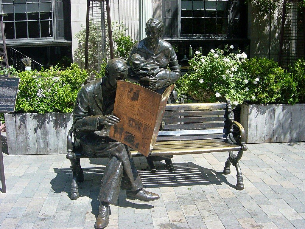 Bronze man sitting on a bench reading newspaper statue