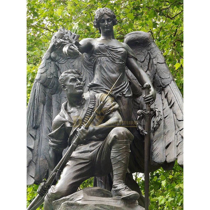 Bronze Depiction Of A Soldier Figure Who Is Protected By An Angel Statue