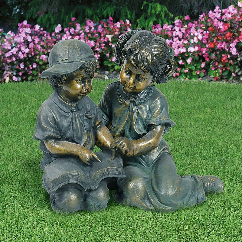 boy and girl reading book garden statue