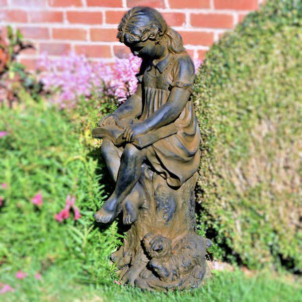 girl reading book garden statue