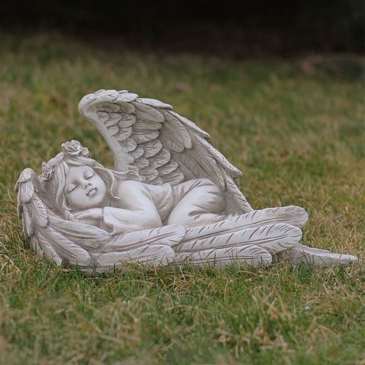 sleeping baby wrapped in angel wings statue