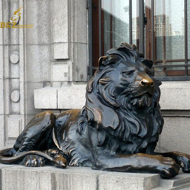 Bronze lion statue lying down outside house