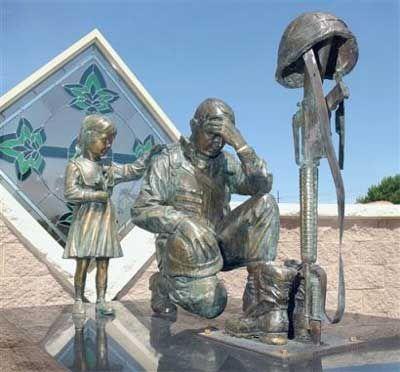 soldier kneeling at the cross